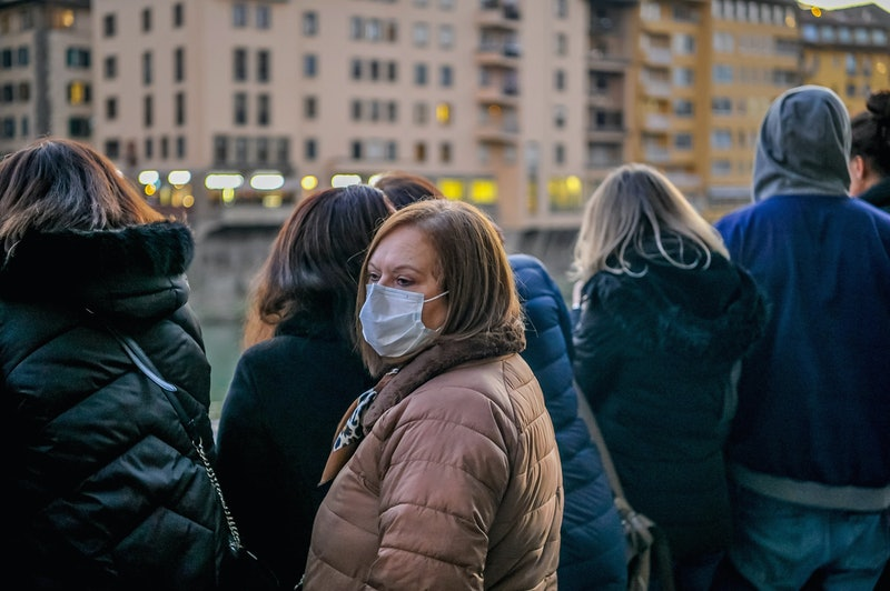 A person stands in a crowded street wearing a mask to filter potential pathogens from the air. The c...