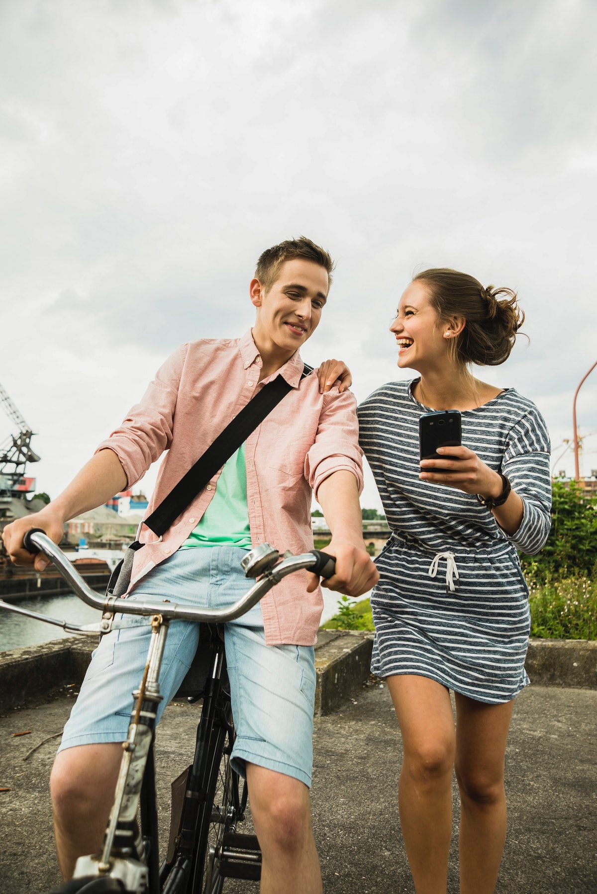 A young couple laughs at a phone while bike riding on a cloudy day.