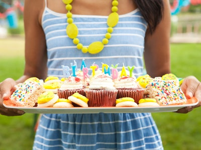 a girl holding a birthday board with cupcakes and other treats