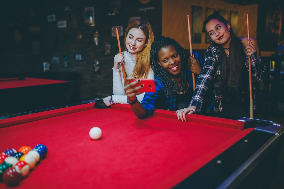 Three friends take a selfie on their phone while playing pool in a bar.