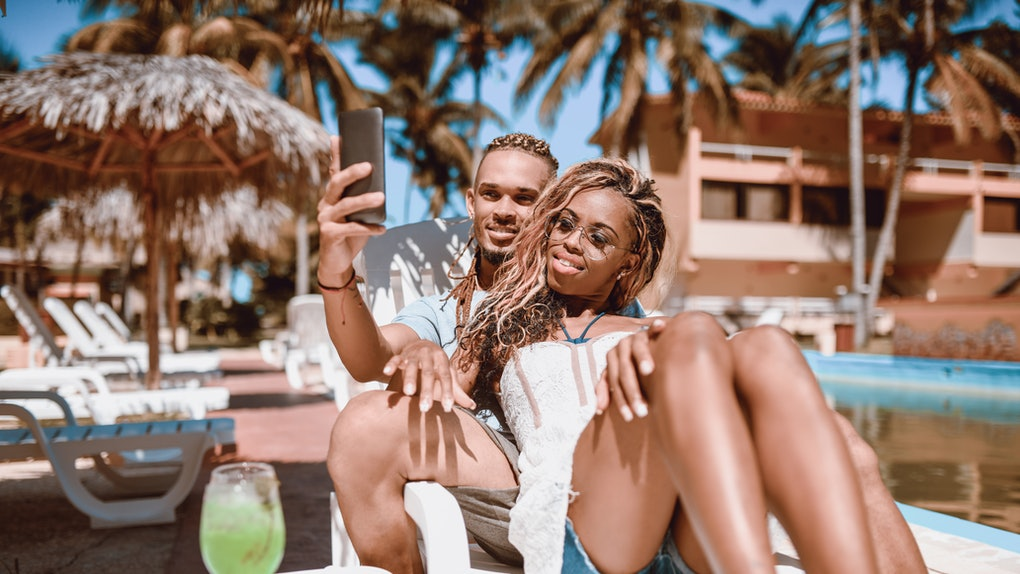A couple relaxes on a lounge chair in the sunshine at a tropical beach resort while posing for a selfie.