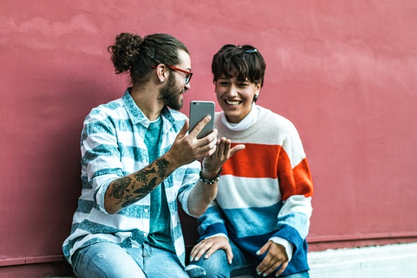 A couple sits against a pink wall in the city and laughs while looking at a phone.