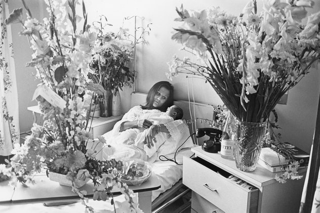 A French maternity ward is full of flowers for this mom and her new baby snuggling in the hospital bed.