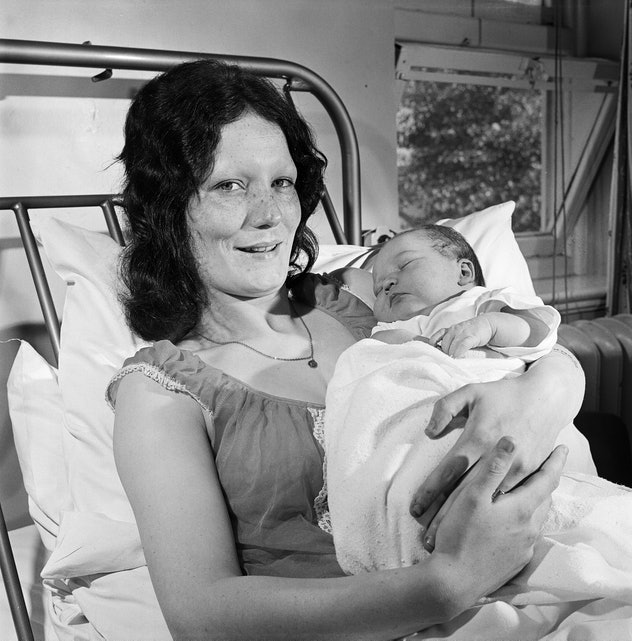 A mom holds her newborn baby with pride in her hospital bed, smiling with tired eyes at the camera.
