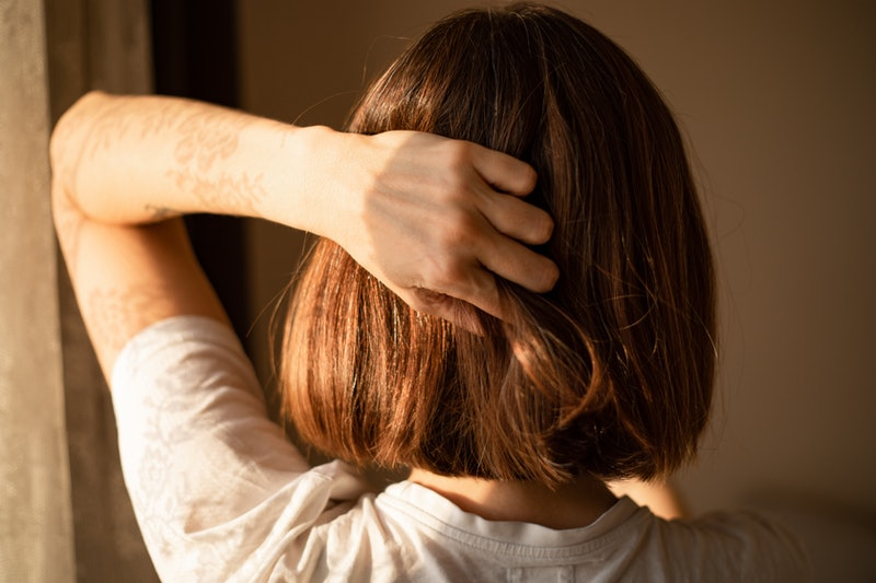 A woman runs her hand through her hair. Endometriosis can cause intense pain, and treatments can include surgery, hormonal treatment, and early menopause.