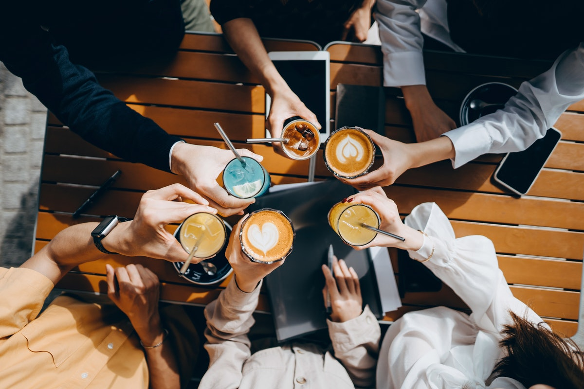 A group of friends holds their cups of coffee together at a coffee shop on a sunny day.