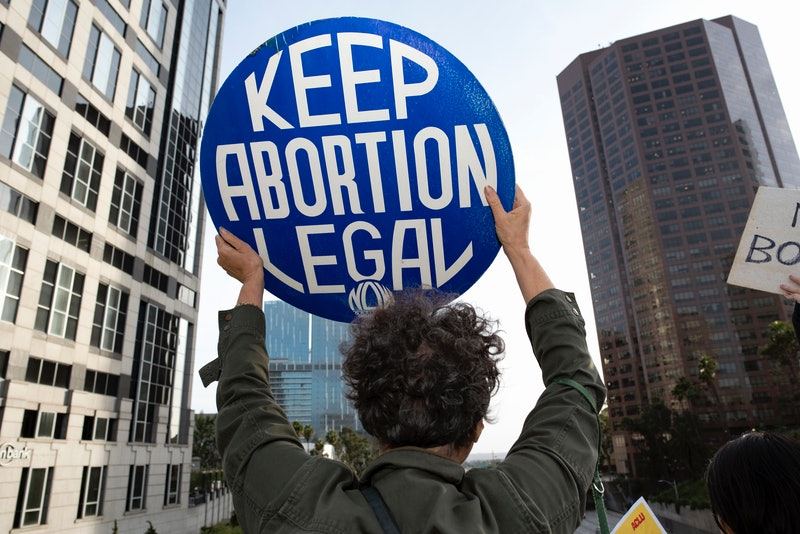 """People standing in a crowd holding signs reading, """"Keep Abortion Legal."""" Virginia lawmakers just removed barriers to abortion access across the state."""