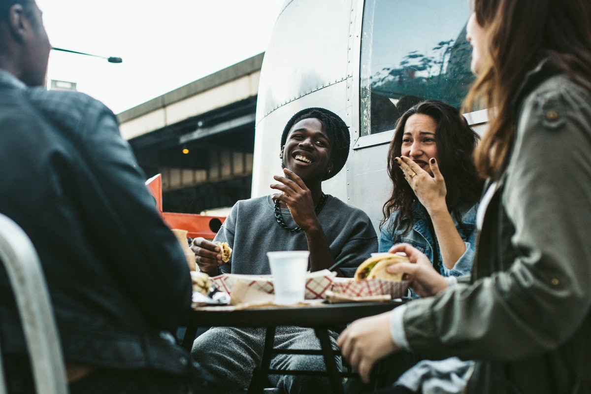 A group of friends laughs while sitting in an outdoor café and eating tacos.