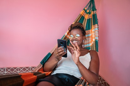 A young woman relaxes in a hammock surrounded by a pink wall while writing a belated birthday messag...