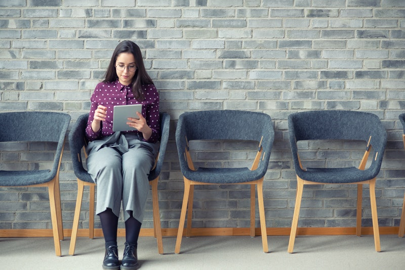 A woman sits in a therapy waiting room, brainstorming what to talk about for a more productive therapy session