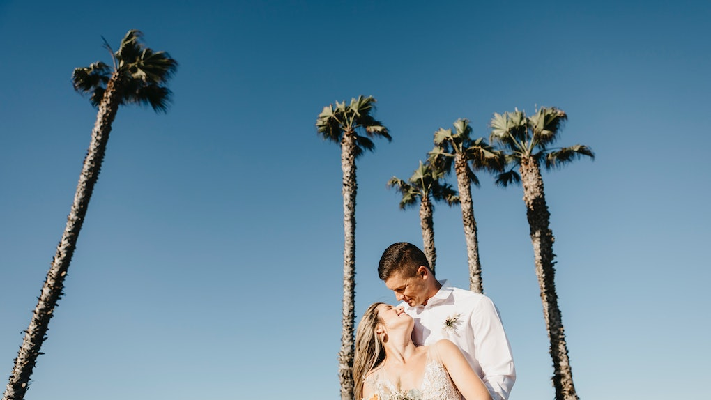A couple stands under palm trees while eloping in California.