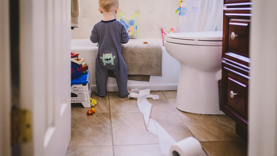 a toddler boy making a mess in the bathroom