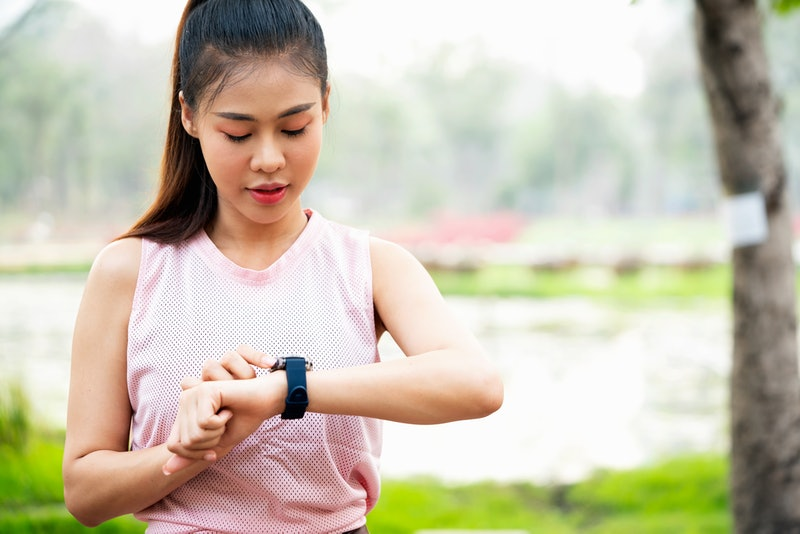 A person wearing a pink mesh tank top checks her smart watch during an outdoor workout. You don't need to count your calories to maintain good heart health.