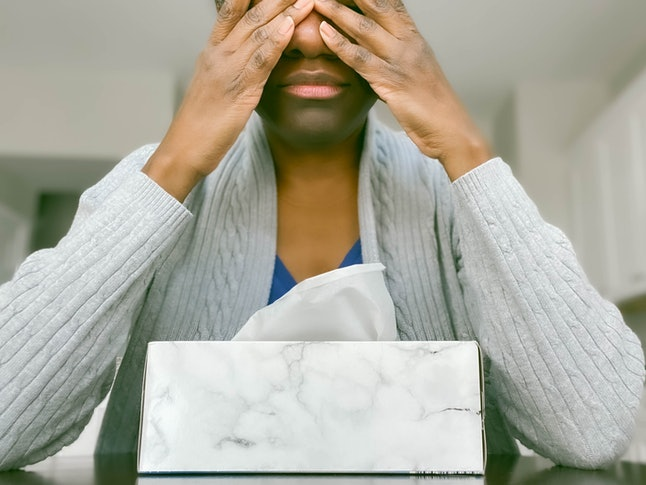 A woman covers her eyes, leaning on a tissue box. Stress has a number of impacts on the body, research shows