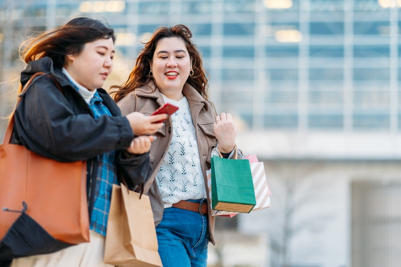 Two people walk together with shopping bags, with one person texting while her friend also looks at ...