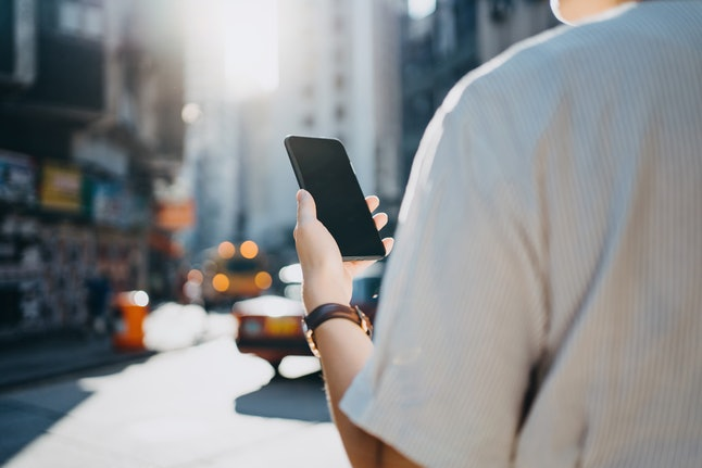 A woman looks at her phone in the middle of the street. Texting while walking is more dangerous than you thought, a new study says.