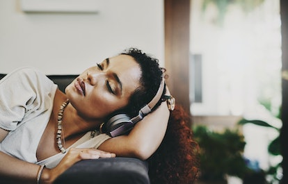 A woman sleeps with headphones. Listening to podcasts with emotional resonance may affect your dreams, particularly in the lighter phases of sleep.