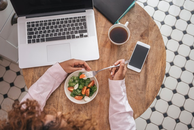 A woman eats a salad at her desk. Making the switch to vegetarianism isn't easy, but it is rewarding.