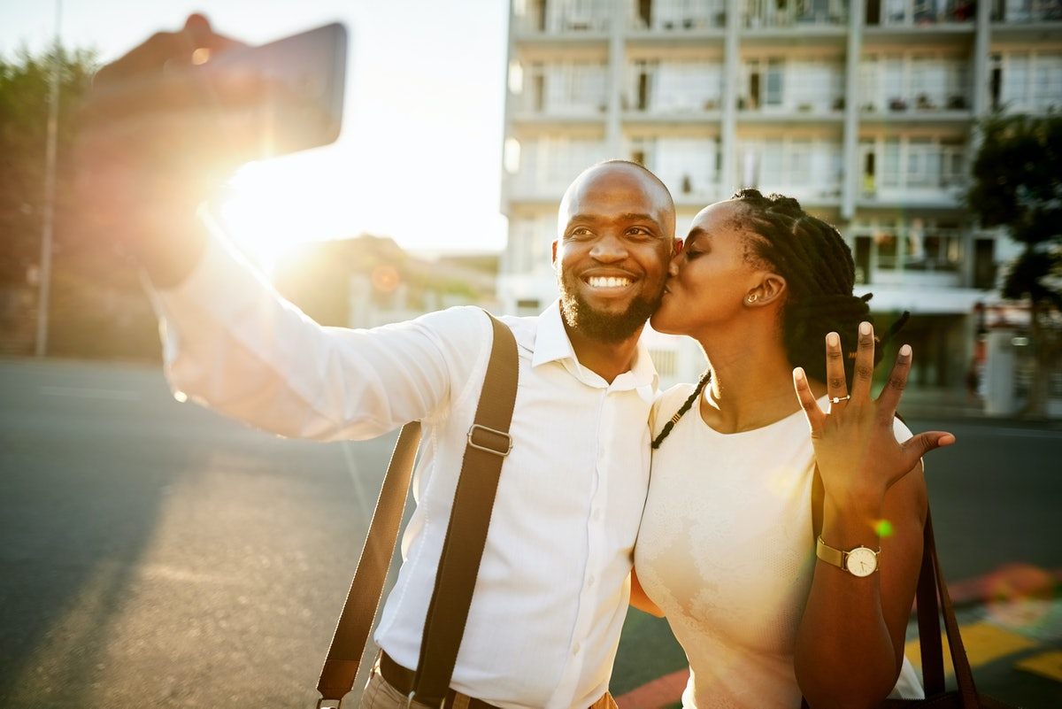 A young couple take a picture on their phone at sunset after getting engaged.