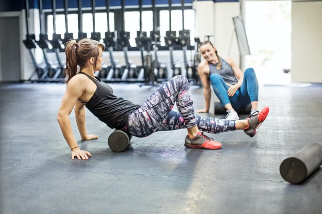 Two people foam roll together on the gym floor. Take it easy when you're coming back to the gym from sickness, experts say.