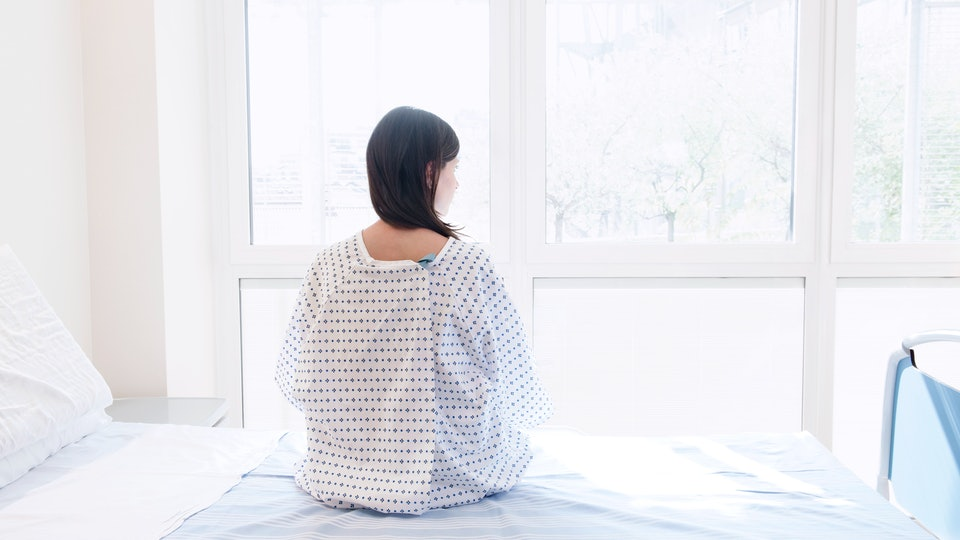 woman in hospital bed looking out window