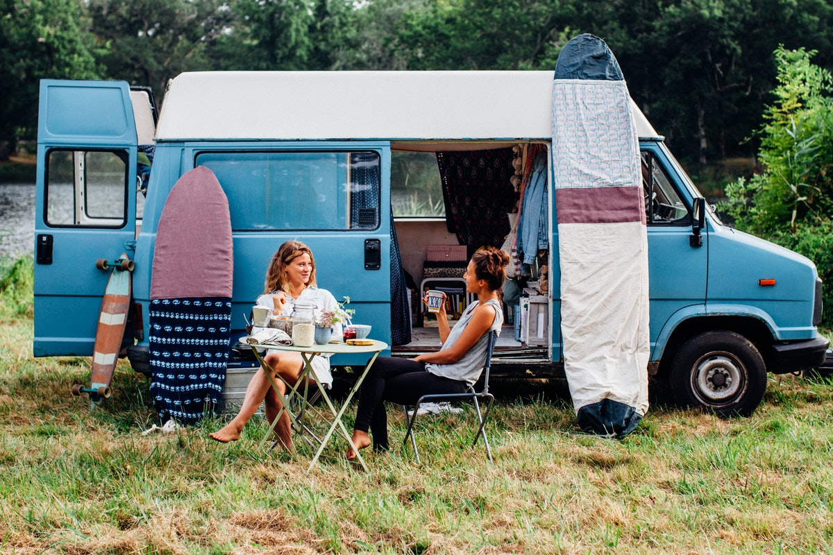Two friends sit outside of their campervan in the middle of spring and eat breakfast.