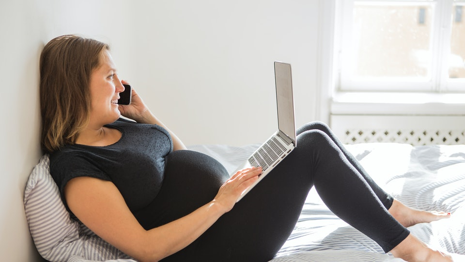 pregnant woman wearing leggings on bed
