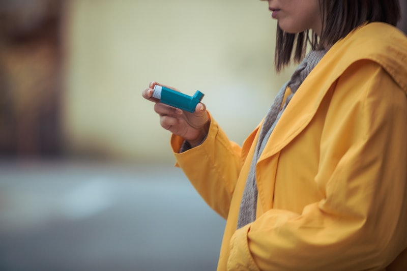 A person wearing a yellow jacket holds up their inhaler. It appears that people with asthma are not more likely than others to get coronavirus, but the respiratory illness might induce asthma attacks.