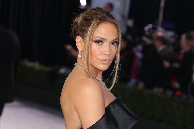 Jennifer Lopez wearing a black dress and diamond jewelry with a tousled updo