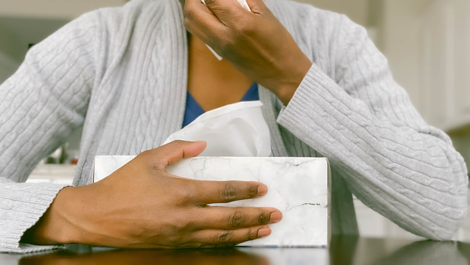 A woman blows her nose. During the coronavirus outbreak, paid sick leave is a major help to containing the virus. Emergency paid sick leave legislation would help support the lowest-paid workers who often lack this access.