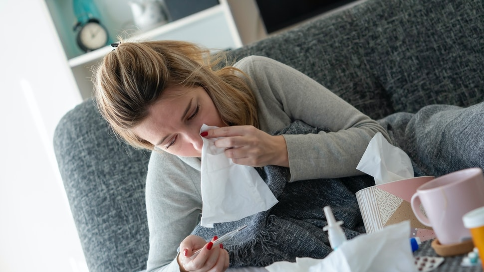 A person with red nail polish holds a tissue to her nose with one hand and holds a thermometer with the other. There are some key differences between coronavirus and allergies to keep in mind as spring approaches.