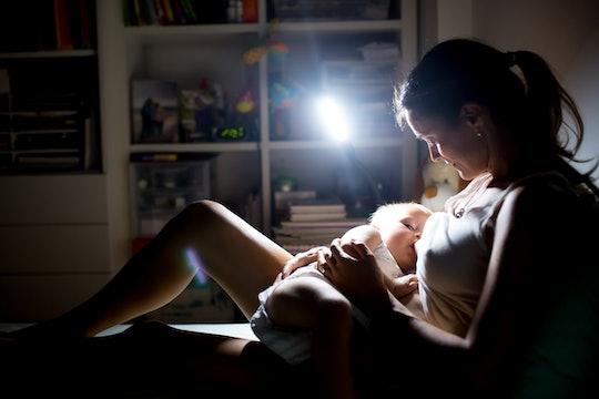 woman nursing baby at night