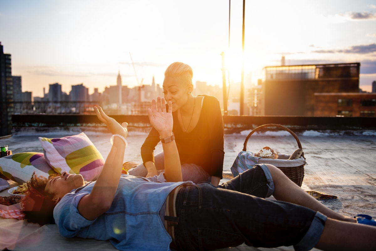 A young couple has a picnic on a rooftop in the city at golden hour.