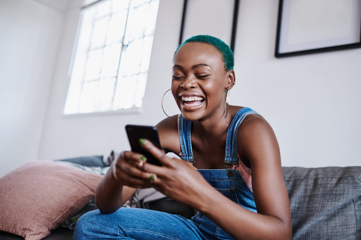 A woman laughs at her phone while sitting on a couch in her apartment.