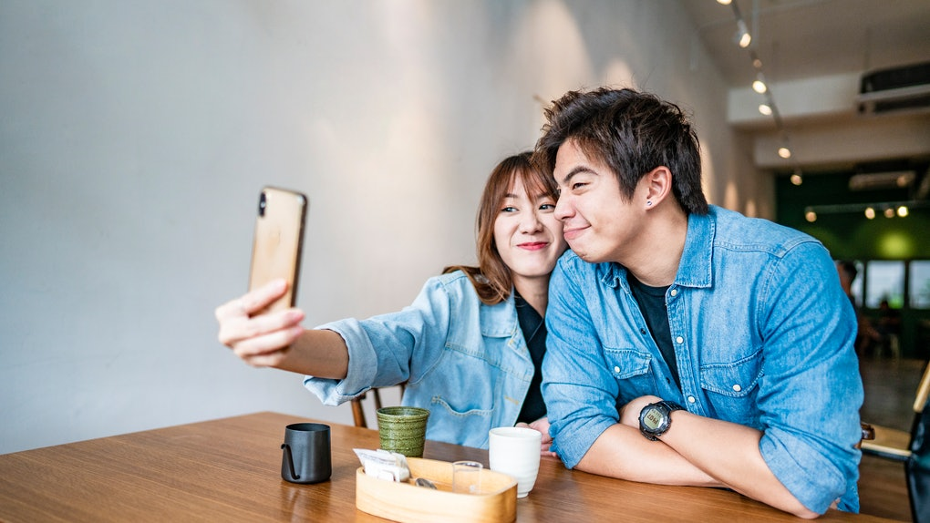 A cute couple takes a funny selfie while sitting at a table in a restaurant.