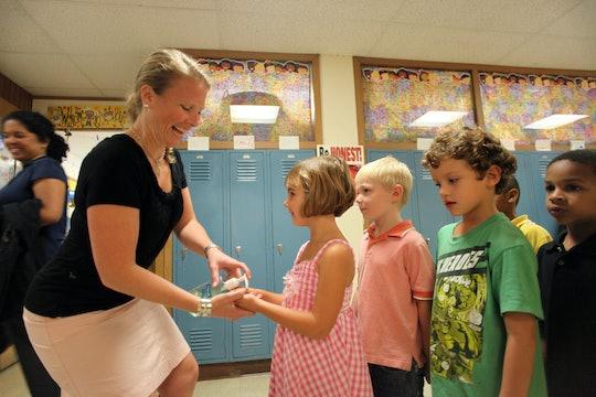 a teacher putting hand sanitizer on kids' hands