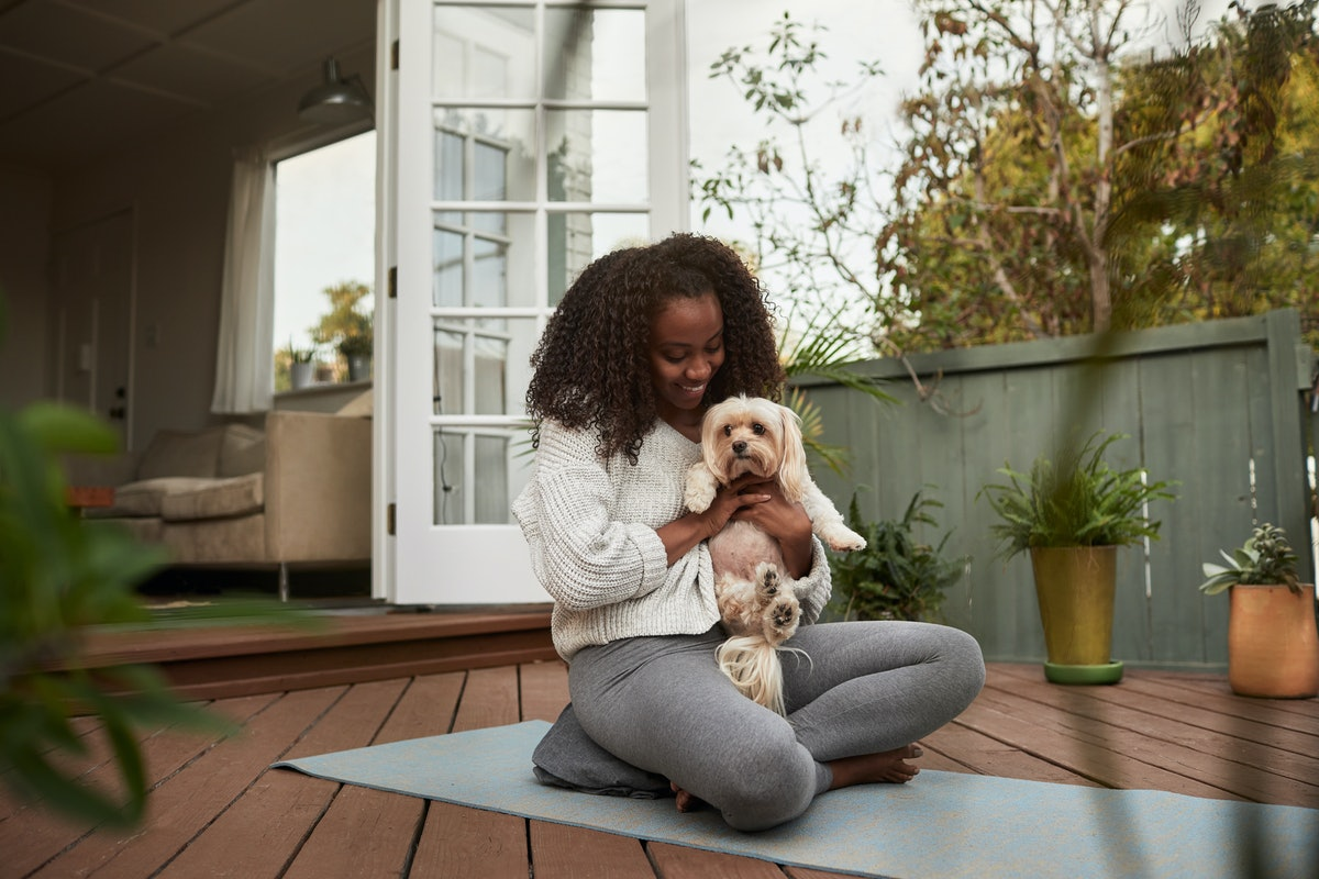 A young woman hangs out with her dog while sitting on a yoga mat on her deck.