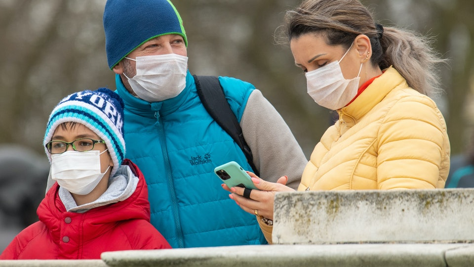 a mother, father, and son all wearing masks outside in a quarantine