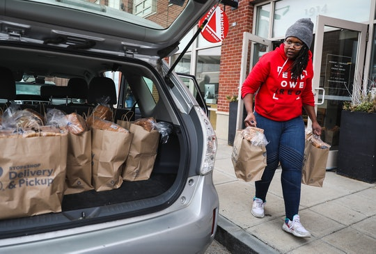 a woman packing food donations into the back of a car