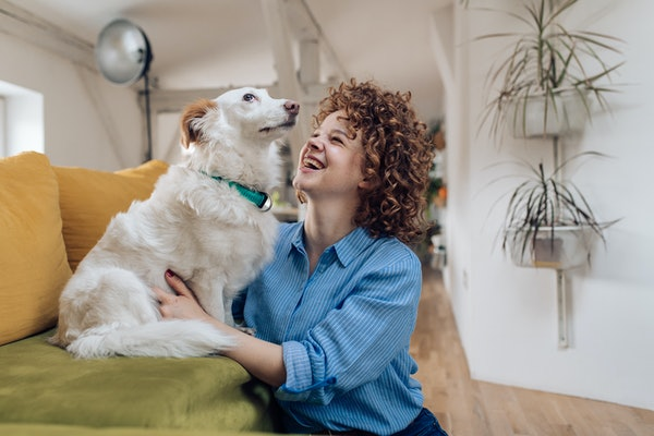 A girl laughs while hanging out at home with her dog.