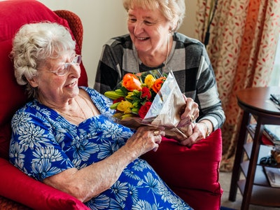 an elderly woman getting flowers in a nursing home