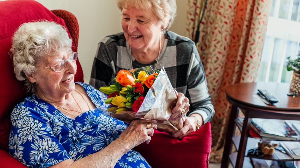 an elderly woman getting flowers in a nursing home