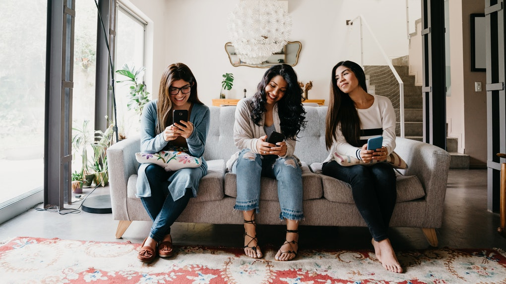 Three girls sit on a couch and play the best iPhone games on their phones.