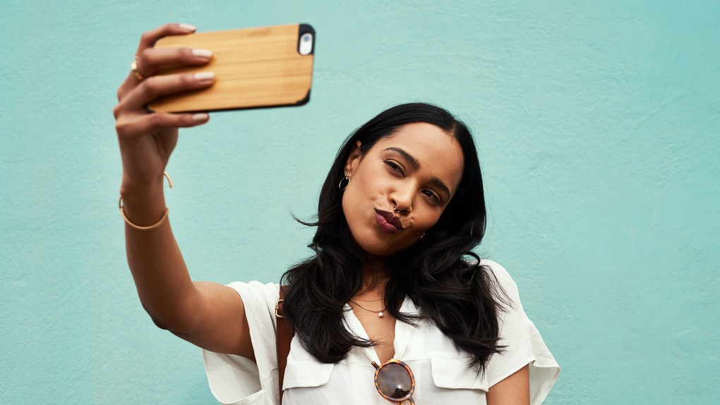 A young woman takes a selfie on her phone in front of a light blue wall.