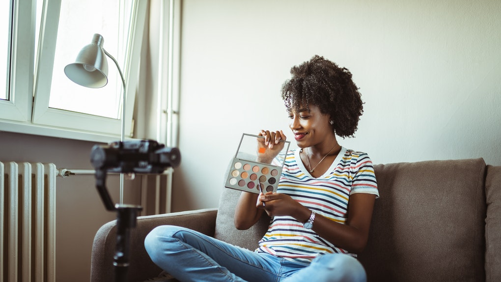 A young woman poses with a set of watercolors while having a photo shoot at home.