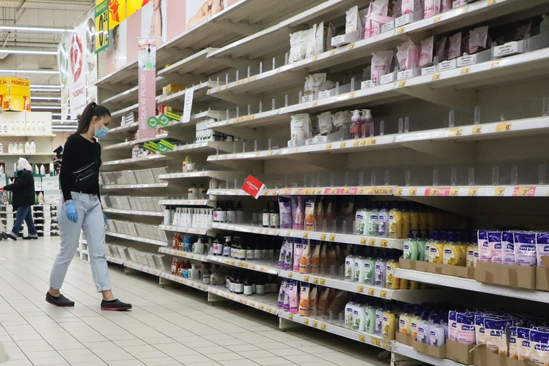 A woman wearing a facemask looks at nearly empty shelves in a pharmacy during the coronavirus pandemic. Is it safe to go to a pharmacy right now? Only if you absolutely must, experts say.