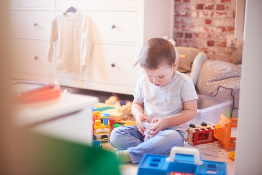 a little boy playing by himself with toys
