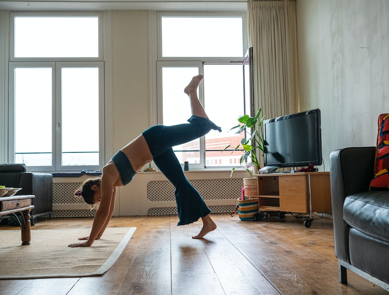 A person performs a down dog split in a living room. If you're concerned about the coronavirus in your gym, you may want to spend a little extra time cleaning the equipment even when you're working out from home.