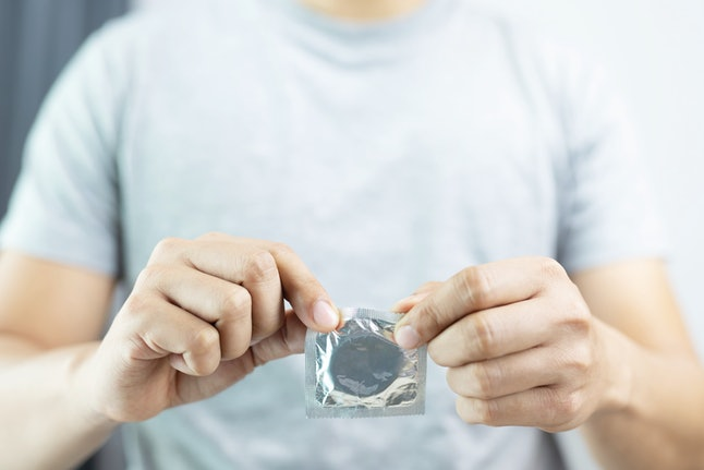 A man rips open a condom to have sex for the first time