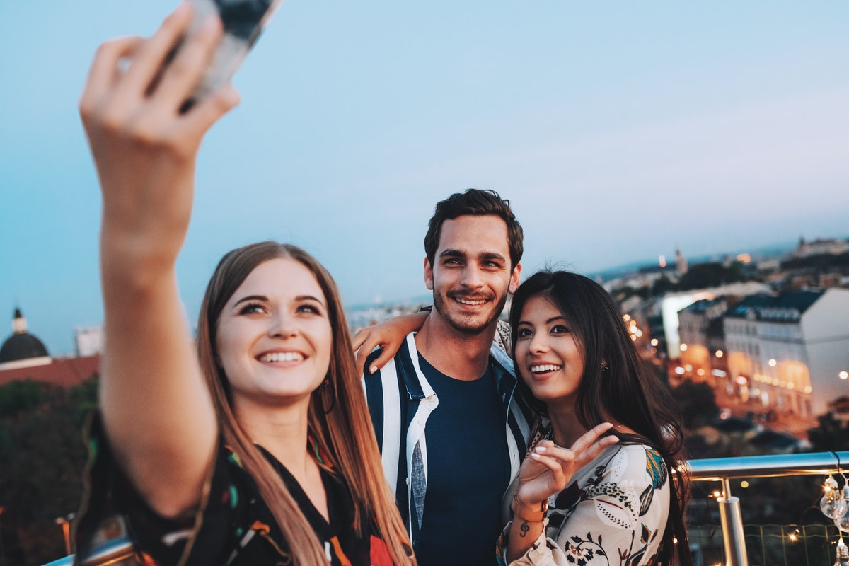 Three friends pose on a rooftop at sunset and take a selfie on their phone.